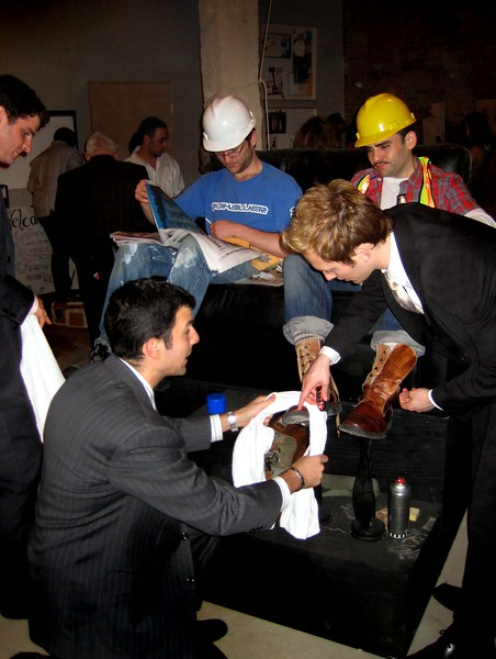"""ShoeShine Project<br /> Performance expressing role reversal of social & economic classes. (Wall street executives shining the boots of construction workers.)<br /> 50"""" x 54"""" x 65""""h<br /> May 2008"""
