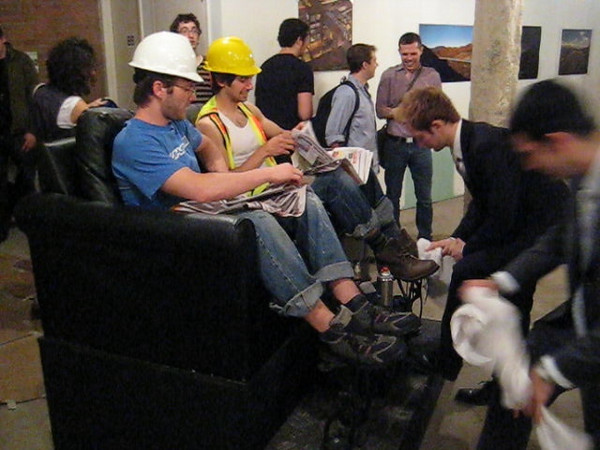 "WATCH VIDEO<br /> ShoeShine Project<br /> Performance expressing role reversal of social & economic classes. (Wall street executives shining the boots of construction workers.)<br /> 50"" x 54"" x 65""h<br /> May 2008"