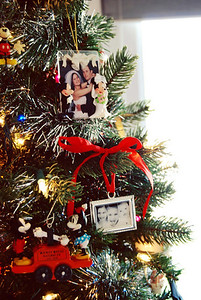"I have a few certain ""rules"" about placing some ornaments (OCD, I know). My wedding picture in the Mickey & Minnie frame *always* gets placed at the top-center of the tree because lets face it, without that event the whole tree wouldn't even be here. ; )  The silver frame hung with red ribbon is a tradition I started last year; making a photo ornament of my three babies each Christmas. This year's ornament is on it's way to our house. Can't wait to see them side-by-side!"