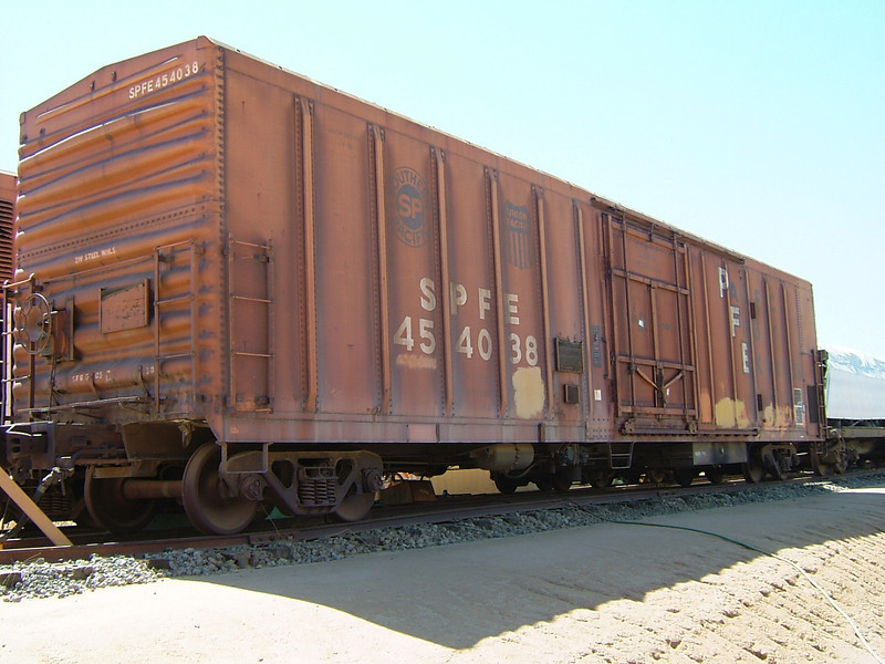 B-end, right side of SPFE 454038.<br /> Low hand brake as-built, running board removed.<br /> 1975 style paint (orange ends, white reporting marks).