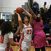 """Dearborn's Layaill """"Lulu"""" Mustafa (23) goes up strong for two of her eight points over Detroit Martin Luther King's Erica Whitley-Jackson (44). The Pioneers were eliminated from the playoffs with a 67-31 loss to MLK in Region 4-A action at Fordson. (MI Prep Zone photo gallery by RYAN DICKEY)"""