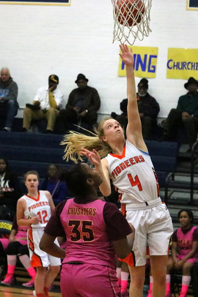Dearborn senior Isabelle Clark (4) gets a layup over Detroit Martin Luther King's Jordan Lewis (35). Clark scored a team-high 10 points in her final varsity game. The Pioneers saw their run in the state tournament halted on Tuesday night with a 67-31 loss to MLK in Region 4-A action at Fordson. (MI Prep Zone photo gallery by RYAN DICKEY)