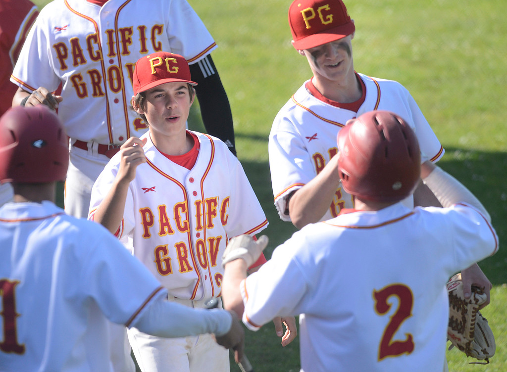 . Pacific Grove\'s Charlie McMahon, center, Hunter Hanes welcome Colby Burnell (2) after he scored against Carmel during baseball at Pacific Grove High School on Wednesday April 19, 2017. PG won the game 4-3. (David Royal - Monterey Herald)