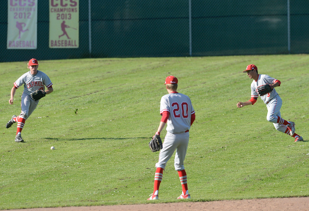 . Carmel\'s Ben Weber, left, and Stevan Enriquez chase down a ball that snuck into the outfield during baseball at Pacific Grove High School on Wednesday April 19, 2017. PG won the game 4-3. (David Royal - Monterey Herald)