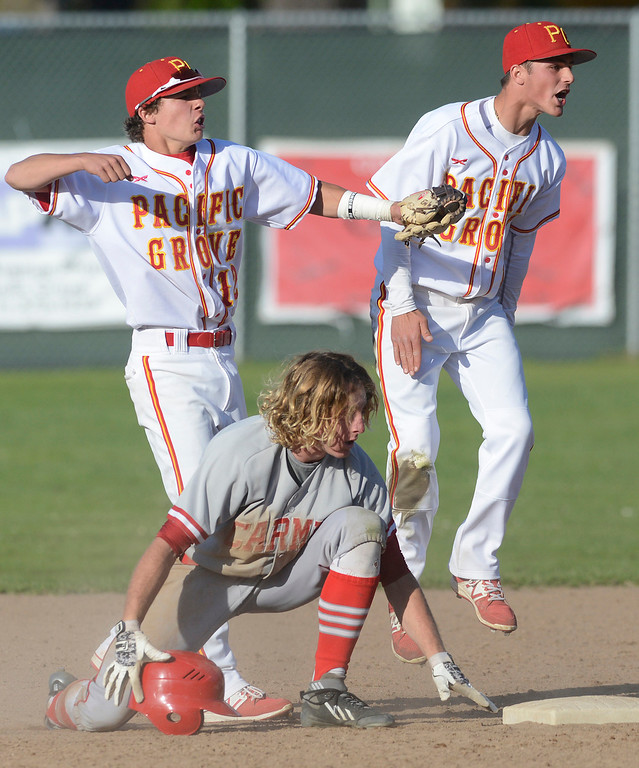 . Pacific Grove shortstop Trevor Heyn, left, and second baseman Anthony Aliotti, right celebrate after Carmel\'s Ben Weber, center, was tagged out after sliding over second base during the sixth inning of baseball at Pacific Grove High School on Wednesday April 19, 2017. PG won the game 4-3. (David Royal - Monterey Herald)