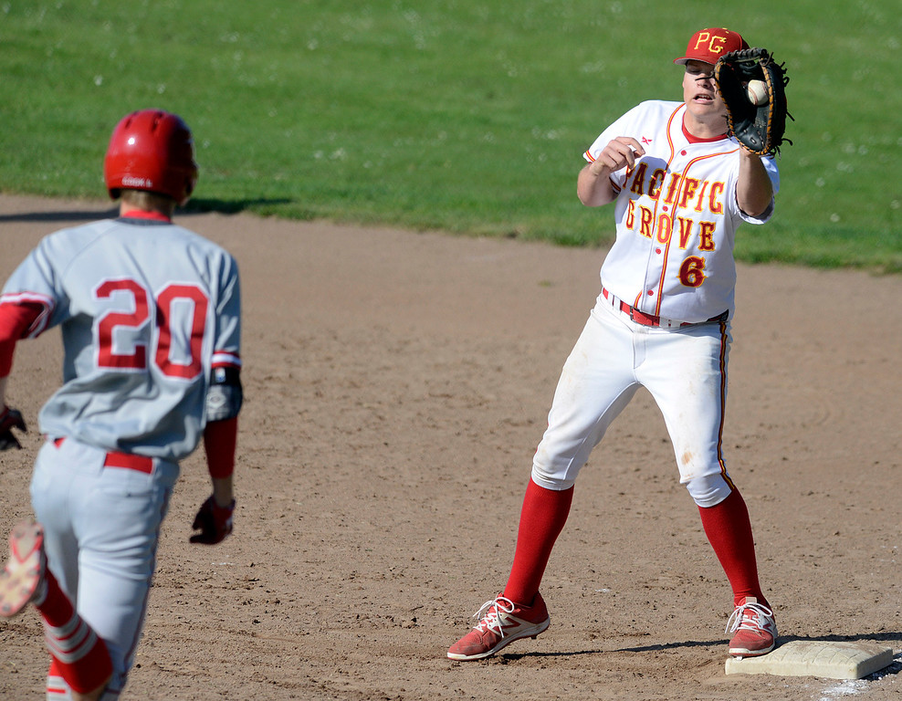 . Pacific Grove\'s River Watts reels in a throw to first base to force out  Carmel\'s Kevin Cook during baseball at Pacific Grove High School on Wednesday April 19, 2017. PG won the game 4-3. (David Royal - Monterey Herald)