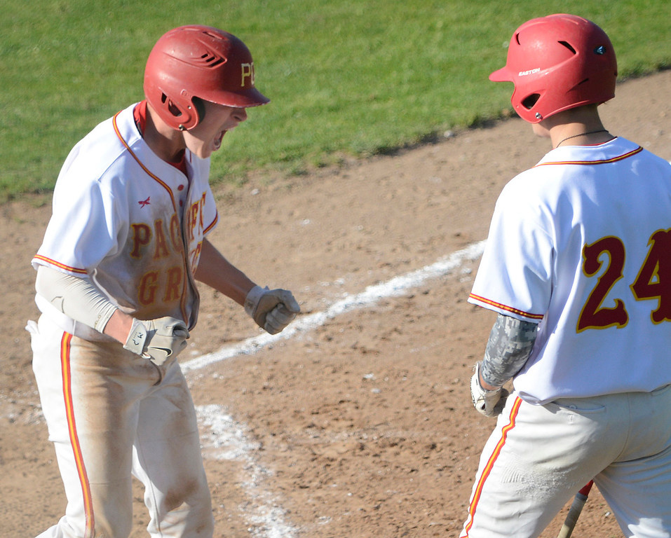 . Pacific Grove\'s Colby Burnell, left, celebrates after sliding safely home to score against Carmel during the fifth inning of baseball at Pacific Grove High School on Wednesday April 19, 2017. PG won the game 4-3. (David Royal - Monterey Herald)