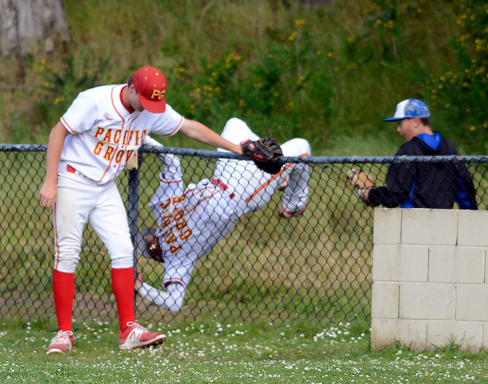 . Pacific Grove second baseman Anthony Aliotti flips over a fence while chasing a foul ball with first baseman River Watts during baseball against Monte Vista Christian in Pacific Grove on Wednesday April 12, 2017. The ball dropped to the ground. (David Royal - Monterey Herald)