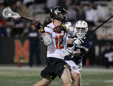 March 31, 2019: Maryland attackman Logan Wisnauskas (12) attempts a shot past an Penn State defenseman during NCAA Mens lacrosse action between Penn State and the University of Maryland in College Park. Photo by: Chris Thompkins/Prince Georges Sentinel
