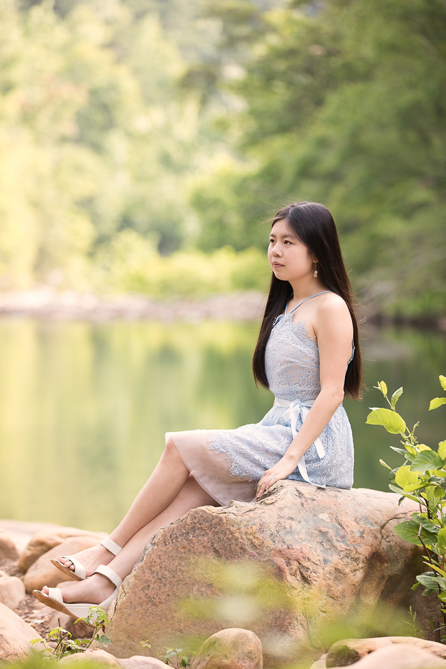 Senior girl posing on rocks by a creek
