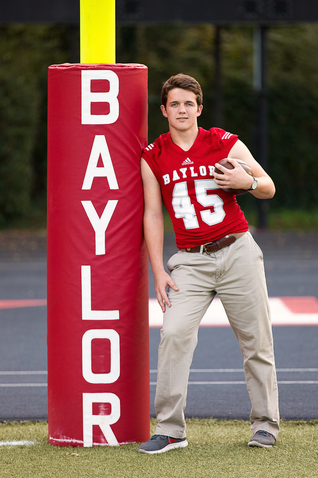 Senior boy in Baylor football jersey on Baylor School football field