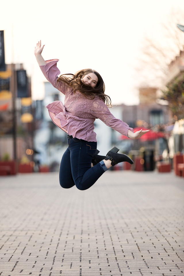 girl jumping in downtown Chattanooga for her senior portraits