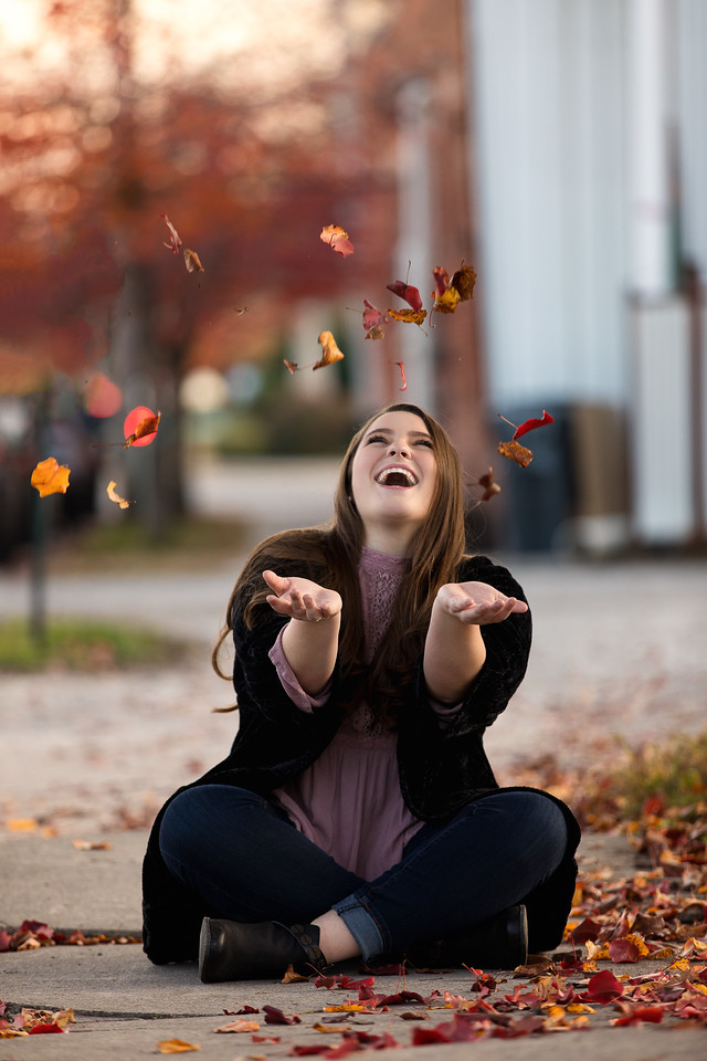 Girl throwing leaves up in the air for her senior portrait in downtown Chattanooga for Pamela Greer Photography