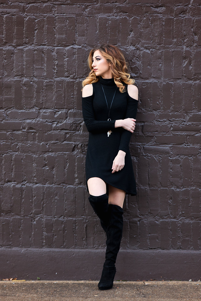 Girl in black dress and black boots leaning against a brown wall for her senior portraits in downtown Chattanooga