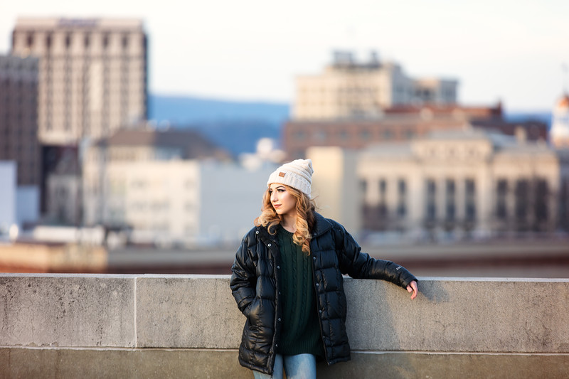 girl in winter coat and hat in front of Chattanooga skyline for her senior photo session