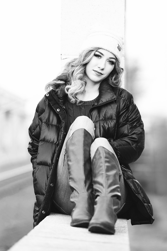 Black and white of girl in a warm winter coat and hat for her senior portraits in downtown Chattanooga