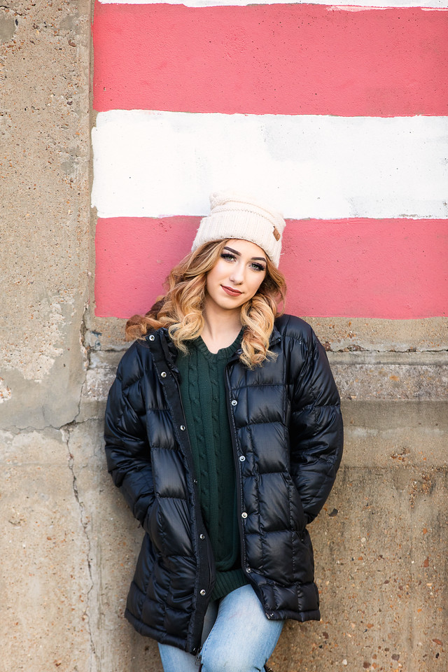 Girl in black coat and hat in front of flag stripes for her senior portrait in downtown Chattanooga