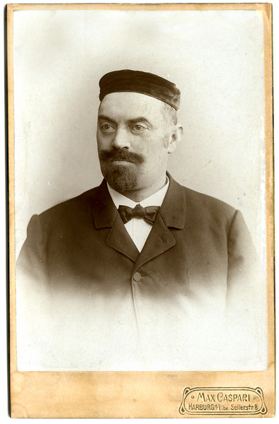 Simon Adler, photo probably shortly after 1900. In 1887 Simon took a cantorial position with the Jewish community of Bunde, Germany, which is 20 km south of Emden, 50km east of Groningen (Niedersachsen). In approximately 1892 he would take a position in Antwerp, Belgium, where Hermann and Hugo (b.1894) were both born.  Then he returned to Hoeringhausen (c.1895).  Records indicate that Ida and Artur, his two youngest children, were born there.  This photo was taken in Harburg, as was the following photo of his wife, Emma Dahl, but at two different studios.  Simon, who died in 1910, is buried in the Hamburg Jewish Cemetery.  (This image required only minor restoration work.)  [ArcAdler 005]