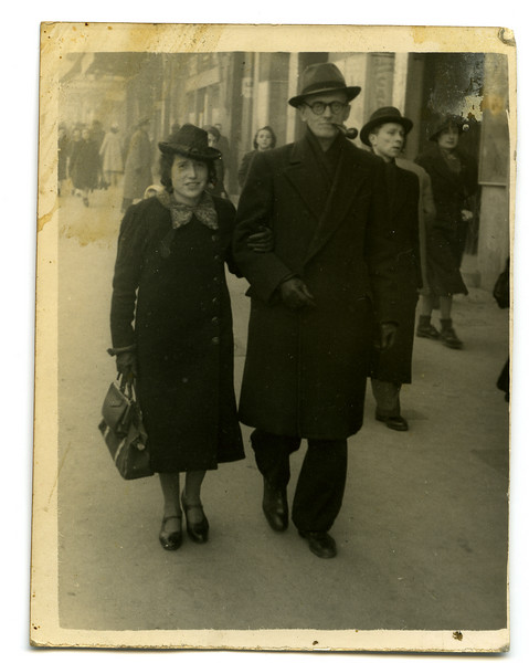 "[Max] Arthur Adler, born in Hoeringhausen, 12 February 1899, and Margot (?); back of photo reads: Marseille, Canebiere 12-12-41, auf dem Wege zum Hafen; Margot traegt die ""bagage."" [on the way to the port, Margot carries the bags] .  This photo is most curious.  It appears to have been casually shot while the couple was walking on the street.  The war was on, of course, so one can only wonder who took the photo and how it ended up in their possession.  Street photographs are frozen moments in time.  Who are the other people on the street?  What happened to them?  When the image is increased in size, one notices that the woman directly over Artur's right shoulder, as well as the woman to the extreme right, are both gazing at the photographer when the image was taken.  The following image is a restored version of this photo.  [ArcAdler 0014]"