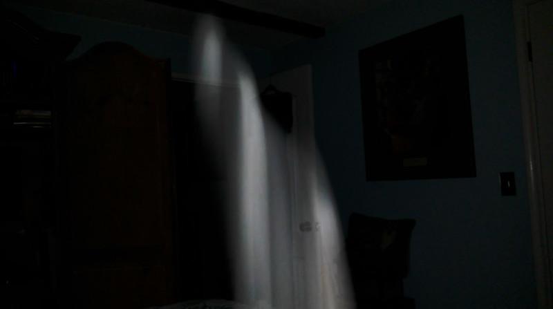 The Light of Jesus descending over my grandmother's wedding dress hanging from the door in my bedroom