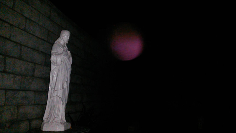 HOW STUNNING IS ARCHANGEL ARIEL??? This is a still image, of The Light of Archangel Ariel, as captured on video the evening of October 10, 2016. On this evening, Ariel was one of three Angels that came forward by my Jesus statue. Ariel lit up the darkness with her deep magenta color, which is a color she often appears in. This is one of my favorite images of Ariel and I told her so. <br /> <br /> Now, by my computer I have a beautiful artist rendering of Archangel Ariel.  The rendering features Ariel as a young woman, with long, auburn colored hair, wearing a purple gown, with large violet colored wings, and a glowing golden crown on top of her head. The day after I captured this image of Ariel, I was working on my computer and I asked Ariel if she liked the artist's rendering of her and she told me NO! I was so surprised because I love the artwork! I asked her if it was the artist's interpretation that she did not like and she told me, so lovingly,  that she did not look like the young woman. She said that I had captured her true essence on camera, so why was I not displaying THIS picture of her beside my computer? OMG!!  Ariel's reply was another God smack moment for me. Needless to say, I immediately printed this image and placed it beside my computer. <br /> <br /> That said, it is important to say that Ariel knows my heart and she understands that I can appreciate, and enjoy, both the artwork and my photograph of her and that each represents a part of my human journey.