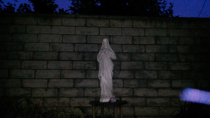 This is one still image, of five images presented, of The Light of Jesus; as captured on video on the evening of June 6, 2017. On this evening, I had placed a purple flower at the base of the statue, so of course, Jesus acknowledged my gesture by appearing as a purple and blue Light!