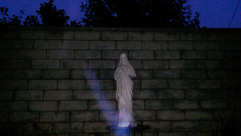 This is the third still image, of five images presented, of The Light of Jesus; as captured on video on the evening of June 6, 2017.On this evening, I had placed a purple flower at the base of the statue, so of course, Jesus acknowledged my gesture by appearing as a purple and blue Light!