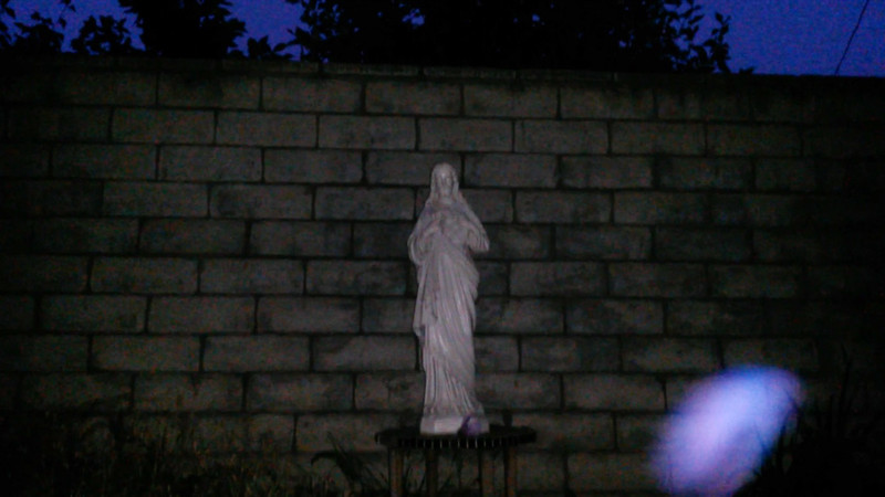 This is the second still image, of five images presented, of The Light of Jesus; as captured on video on the evening of June 6, 2017. On this evening, I had placed a purple flower at the base of the statue, so of course, Jesus acknowledged my gesture by appearing as a purple and blue Light!