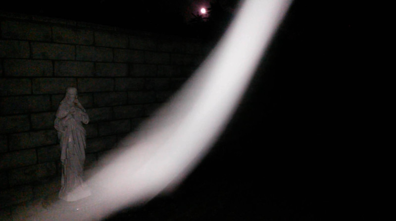 """This is the second still image, of three images presented, of the stunning Light of Jesus descending by my Jesus statue; as captured on  video the evening of the full """"Blue Moon,"""" May 21, 2016. Note how His Light is not obstructing the full moon in the background since He knew I wanted the moon as part of the image!"""