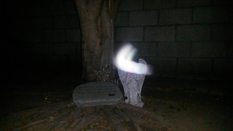 In this image, The Light of Mother Mary was making a turn over the top of the Angel statue in preparation for morphing into a dozen orbs that extended out from the Angel's face. <br /> <br /> This is the thirty-ninth still image, of forty images presented, of The Light of Mother Mary; as captured on video the evening of June 13, 2016.