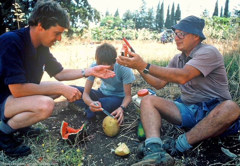 Members of Kibbutz Malkiya take a break at midday in the watermelon and cantaloupe fields.  Some members of the kibbutz are US residents who have made the migration to Israel as part of a personal journey to find and experience their Jewish heritage.  As part of the transition, some temporary and some longer term, the members bring skills from the US, such as clinical psychology, and they work for pay in the communities near the kibbutz and return some or all of the money back to the kibbutz farming community while maintaining a farming work schedule as well.  This keeps them active in their professions while giving back to the kibbutz.