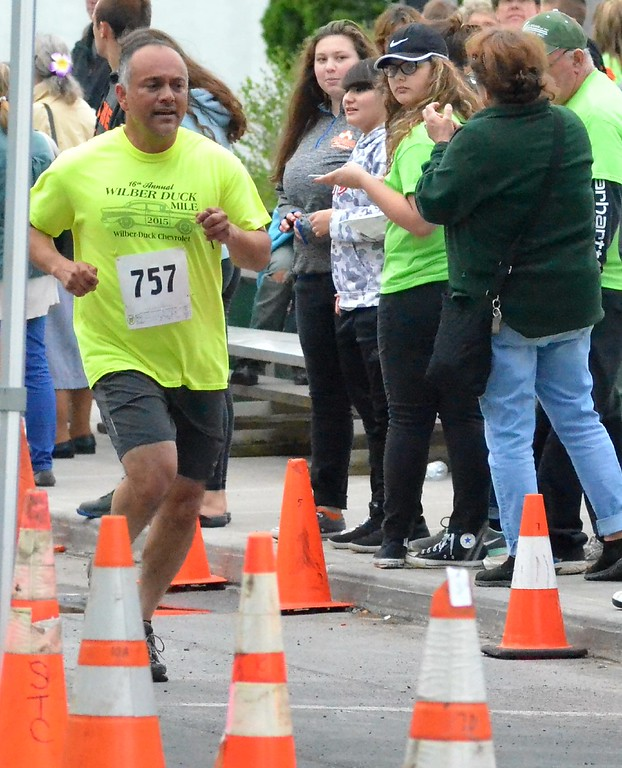 . KYLE MENNIG - ONEIDA DAILY DISPATCH Javier Martinez, winner of the first Wilber-Duck Mile, crosses the finish line at the 18th annual Wilber-Duck Mile in Oneida on Friday, May 19, 2017.