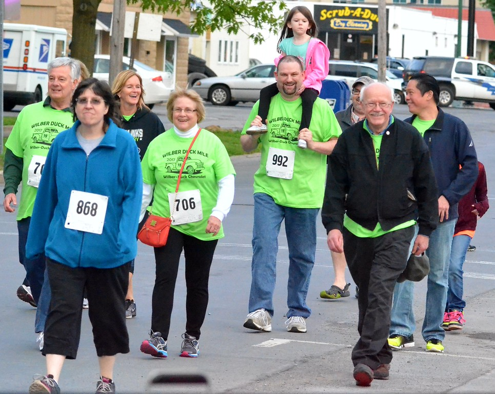 . KYLE MENNIG - ONEIDA DAILY DISPATCH Walkers cross the finish line at the 18th annual Wilber-Duck Mile in Oneida on Friday, May 19, 2017.