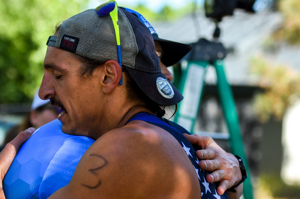 . Robby Chalfant hugs first-place finisher Matt Malone at the finish line of the Lake to Lake Triathlon on Saturday June 23, 2018 at North Lake Park in Loveland. (Cris Tiller / Loveland Reporter-Herald)