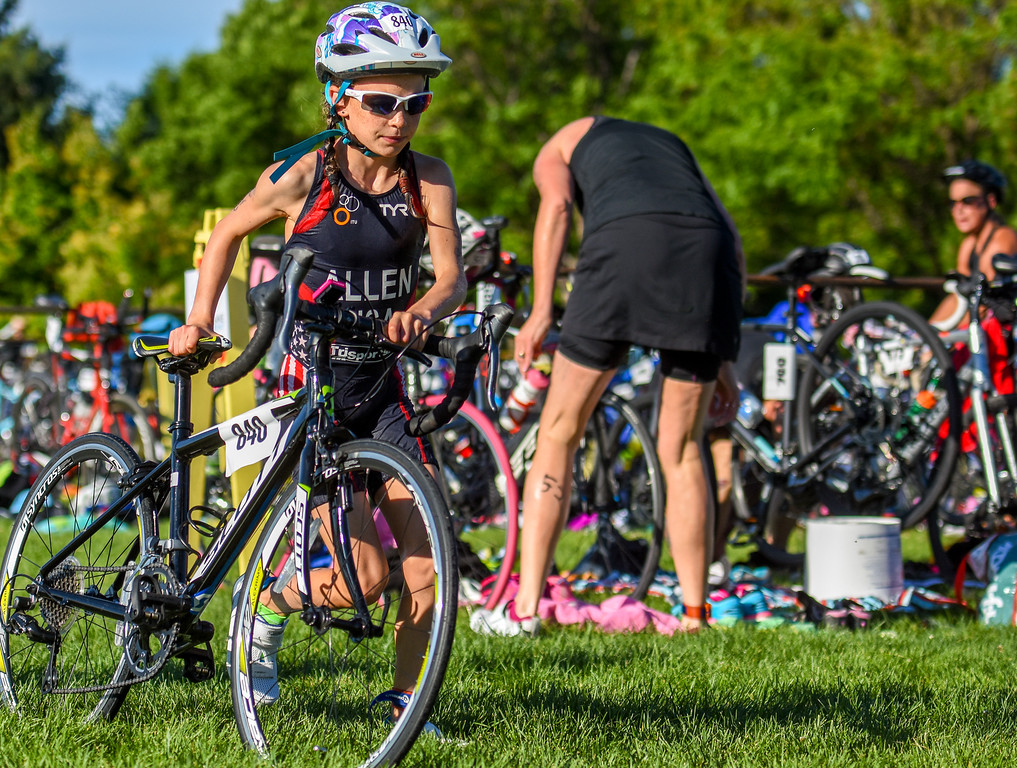 . One of the top 17 ad under competitor exits the bike staging area during the Lake to Lake Triathlon on Saturday June 23, 2018 at North Lake Park in Loveland. (Cris Tiller / Loveland Reporter-Herald)