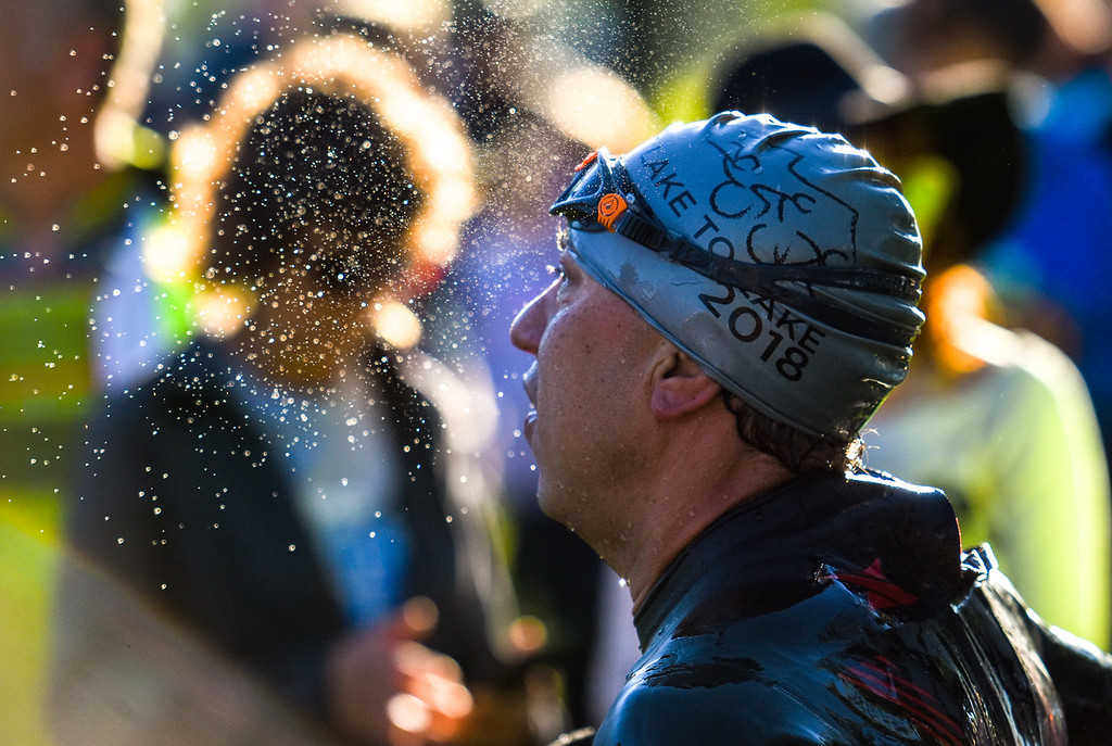 . Beads of water spray into the early-morning sunlight of a competitor during the Lake to Lake Triathlon on Saturday June 23, 2018 at North Lake Park in Loveland. (Cris Tiller / Loveland Reporter-Herald)