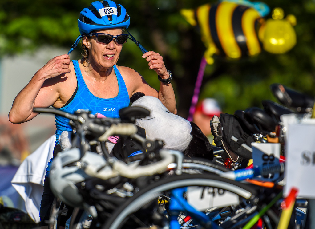 . A competitor secures her helmet before the bike stage of  the Lake to Lake Triathlon on Saturday June 23, 2018 at North Lake Park in Loveland. (Cris Tiller / Loveland Reporter-Herald)
