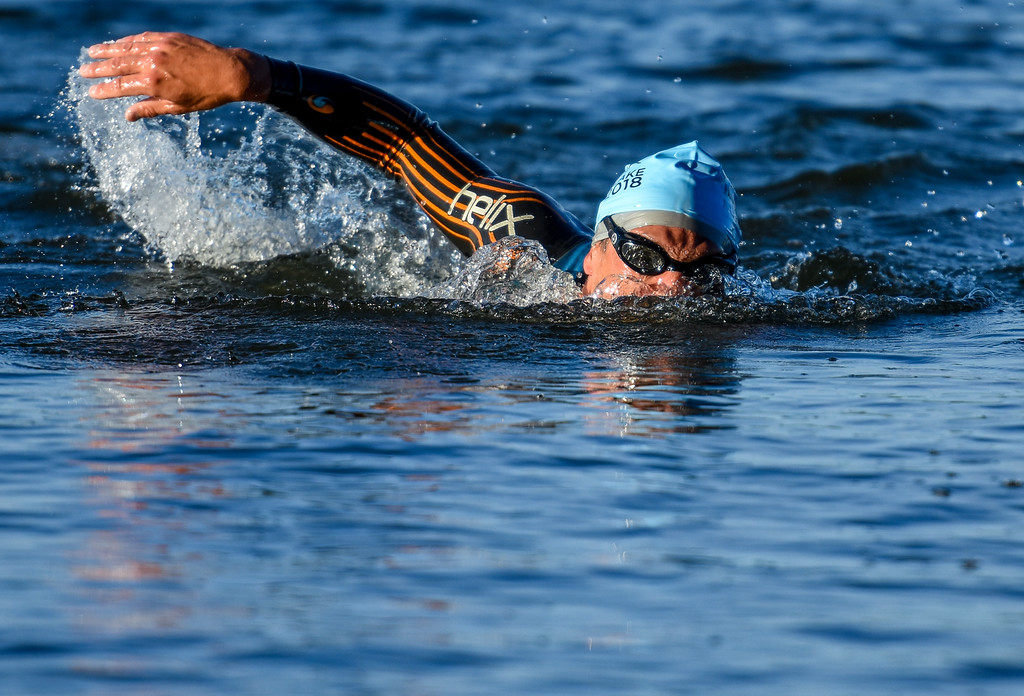 . A swimmer pierces through the water during the Lake to Lake Triathlon on Saturday June 23, 2018 at North Lake Park in Loveland. (Cris Tiller / Loveland Reporter-Herald)