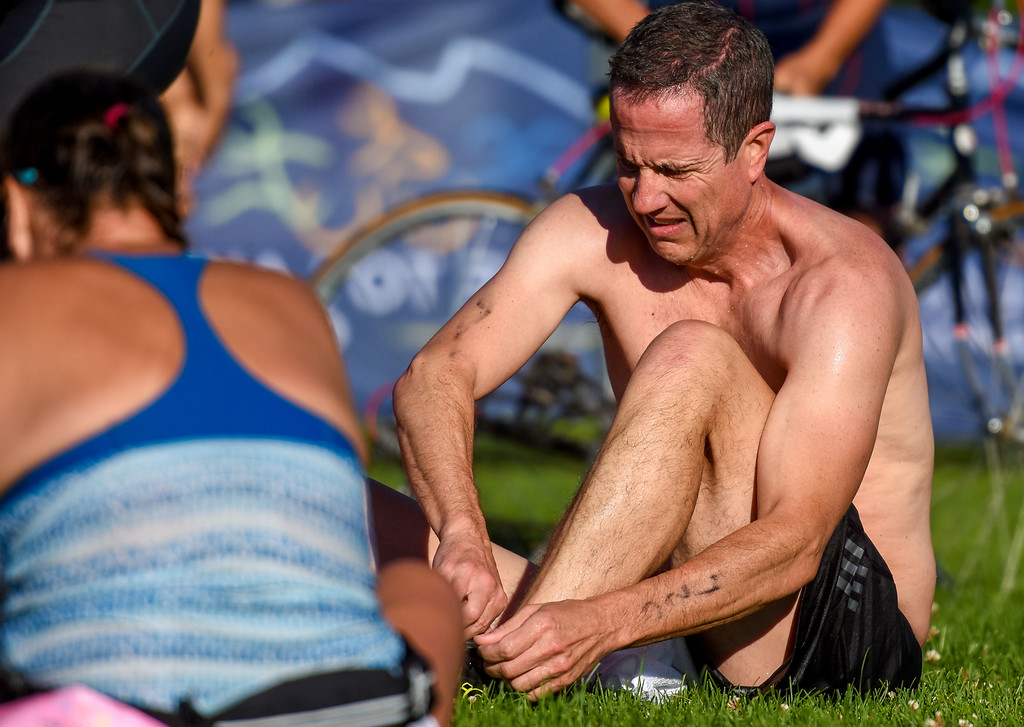 . A competitor puts his shoes on before the biking portion of  the Lake to Lake Triathlon on Saturday June 23, 2018 at North Lake Park in Loveland. (Cris Tiller / Loveland Reporter-Herald)