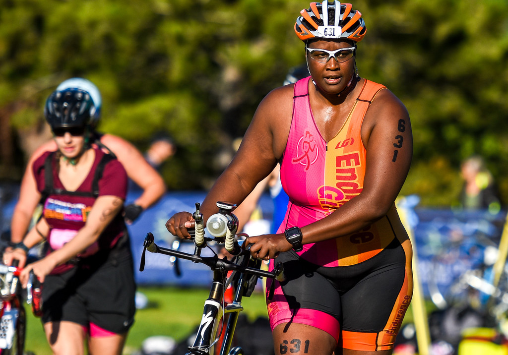 . A competitor exits the bike staging area during the Lake to Lake Triathlon on Saturday June 23, 2018 at North Lake Park in Loveland. (Cris Tiller / Loveland Reporter-Herald)