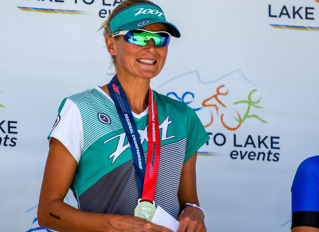 . Top overall female finisher Uli Bromme smiles upcon receiving her medal and prize money after the Lake to Lake Triathlon on Saturday June 23, 2018 at North Lake Park in Loveland. (Cris Tiller / Loveland Reporter-Herald)