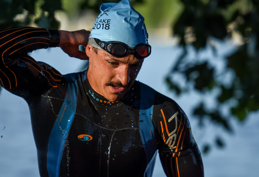. Robby Chalfant goes to unzip his wetsuit after the swimming portion of the Lake to Lake Triathlon on Saturday June 23, 2018 at North Lake Park in Loveland. (Cris Tiller / Loveland Reporter-Herald)
