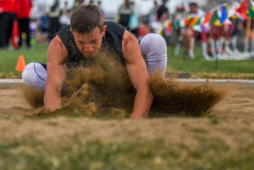 . Berthoud\'s Wyatt Woodrick plunges into the long jump pit during the R2J Meet on Thursday April 12, 2018 at LHS. (Cris Tiller / Loveland Reporter-Herald)