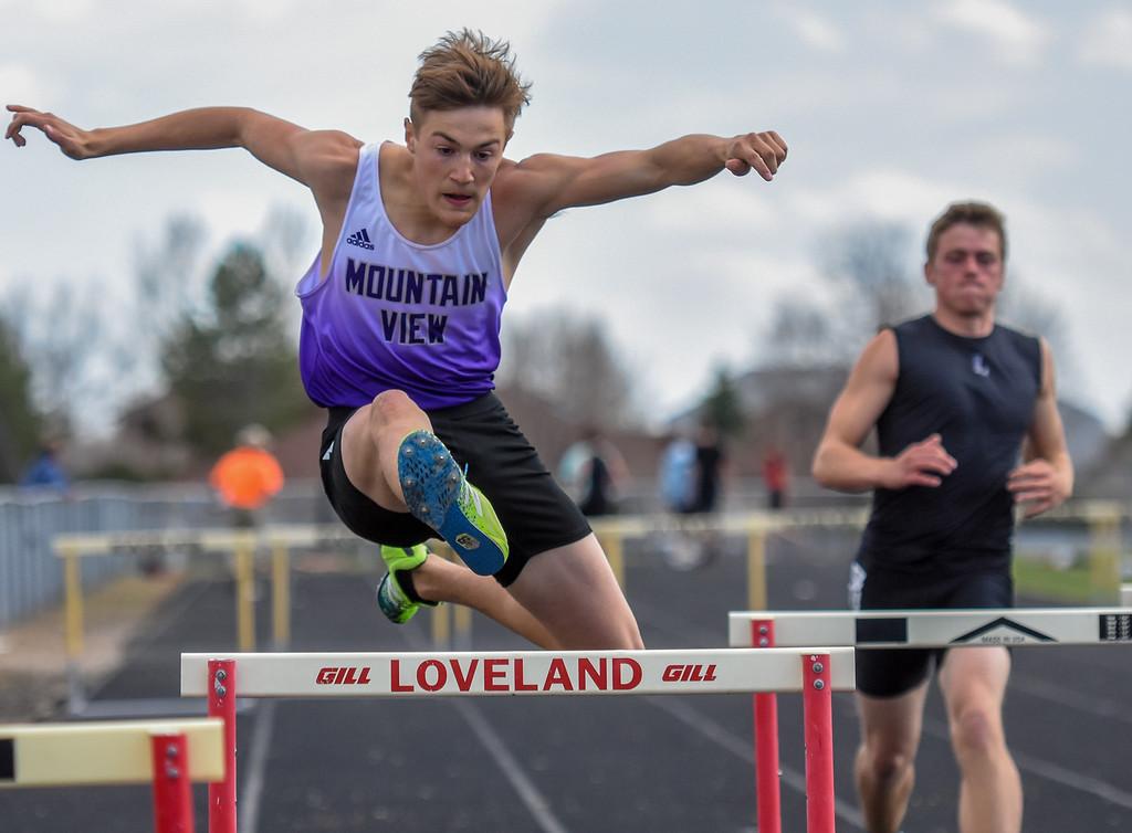 . Mountain View\'s Tanner Kufeld runs the 300-meter hurdles during the R2J Meet on Thursday April 12, 2018 at LHS. (Cris Tiller / Loveland Reporter-Herald)