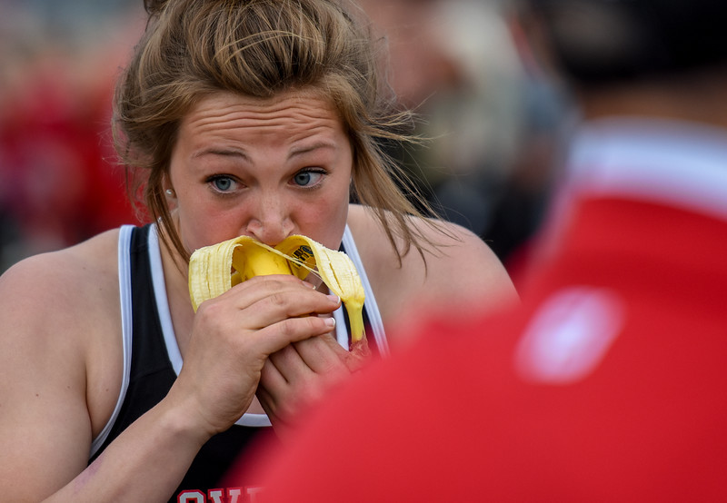 Loveland's Moira Dillow scarfs up a banana at the end of the exhibition 4x50 meter relay during the R2J Meet on Thursday April 12, 2018 at LHS. (Cris Tiller / Loveland Reporter-Herald)