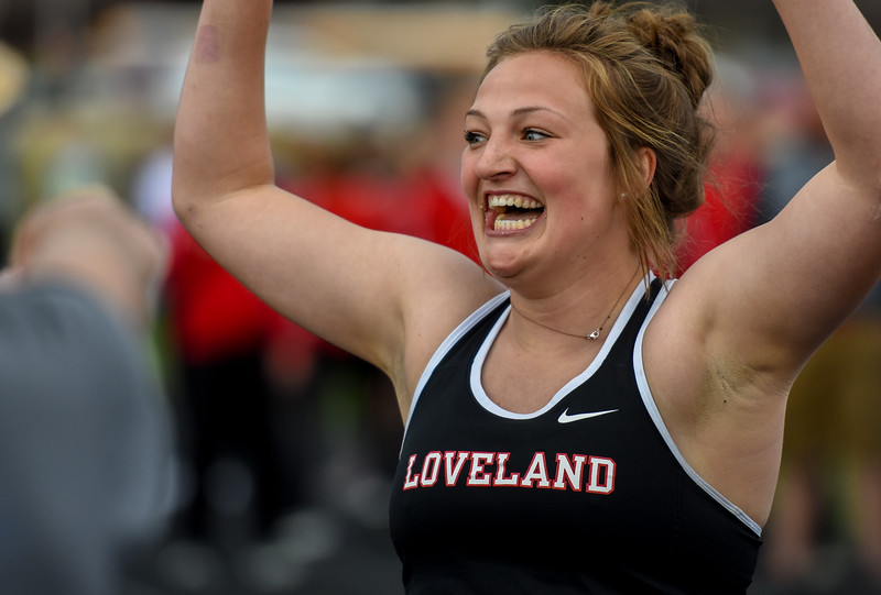 Loveland's Moira Dillow celebrates after winning the girls 4x50 meter relay, which involved finishing an entire banana to win the exhibition event during the R2J Meet on Thursday April 12, 2018 at LHS. (Cris Tiller / Loveland Reporter-Herald)