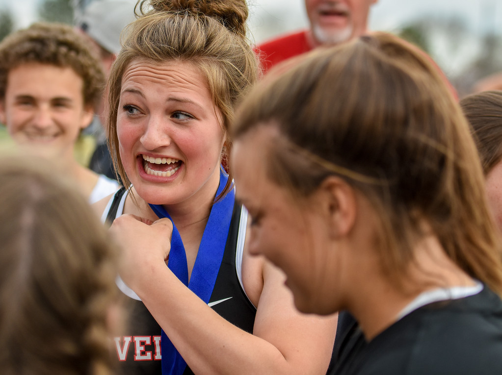 . Teammates placed the first-place medal around the neck of Loveland\'s Moira Dillow after winning the exhibition 4x50 meter relay during the R2J Meet on Thursday April 12, 2018 at LHS. (Cris Tiller / Loveland Reporter-Herald)