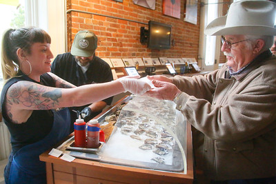Shaun Walker — The Times-Standard  Shannon Donohue, left, and new Humboldt Bay Provisions owner Sebastian Elrite give two raw Bucksport oysters with different sauces to Duane Fredrickson of Iaqua during A Taste of Main Street in Eureka on Friday.