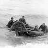 U.S doughboys are brought ashore on the Northern Coast of France following the D-Day invasion of Normandy in World War II on June 13, 1944. The exhausted soldiers on the rubber life raft are being pulled by a group of comrades. (AP Photo/U.S. Army Signal Corps)
