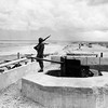 """One year after the D-Day landings in Normandy, a lone U.S. soldier guards a knocked out German gun position on """"Utah"""" Beach, France, May 28, 1945. (AP Photo/Peter J. Carroll)"""